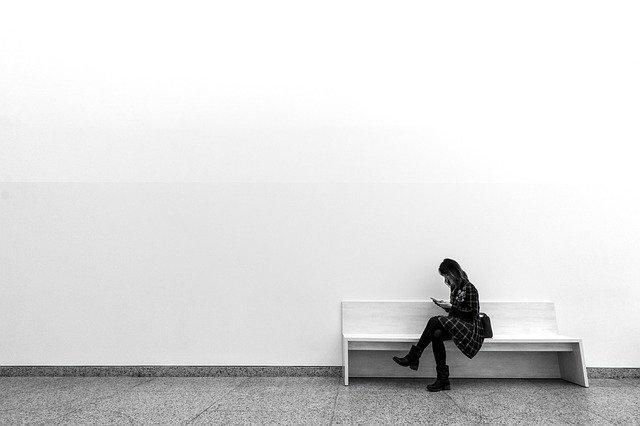 白い部屋で一人スマホをいじる女性